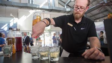 A bartender pours a drink at the 2018 Farm to Table Dinner