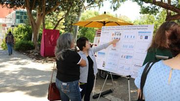 A student explains her research project poster to a visitor.