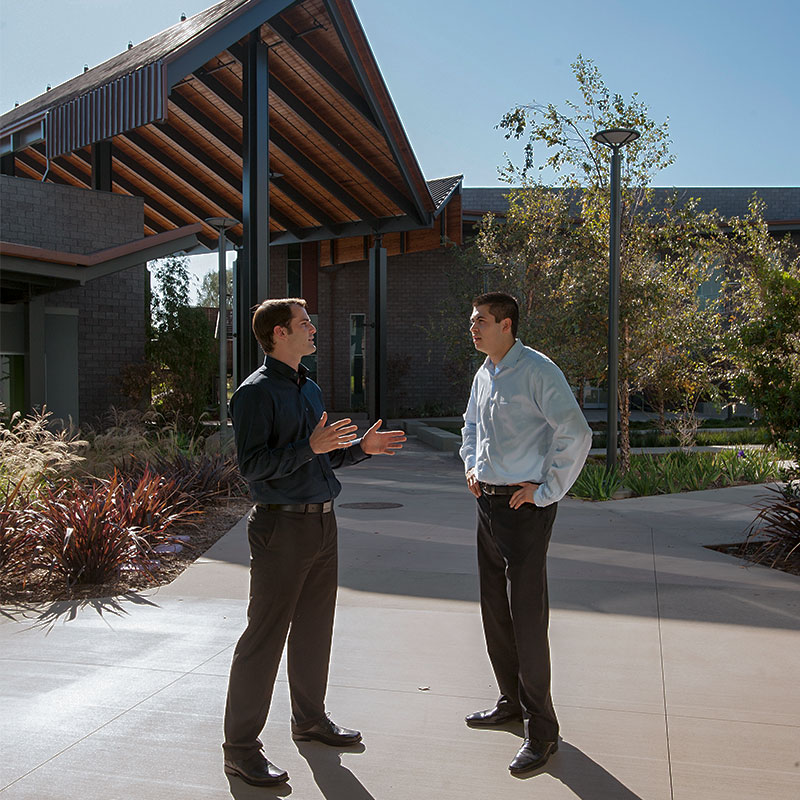 Two male students talking in CBA Courtyard