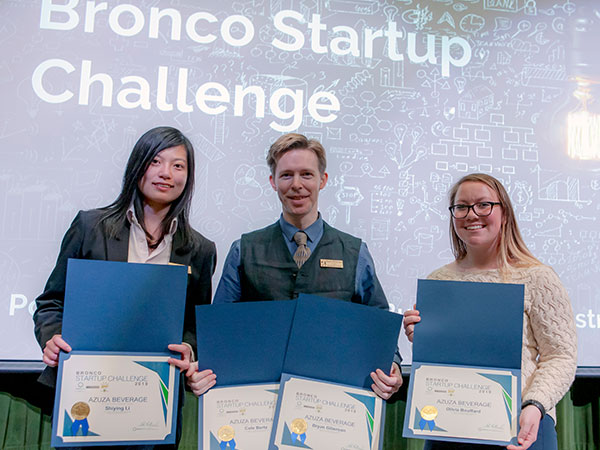 Members of AZUZA Beverage hold winners certificates on stage during Bronco Startup Challenge