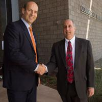Two men shaking hands in front of the CBA