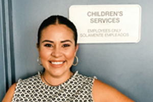 camille delgadillo poses by sign saying children services