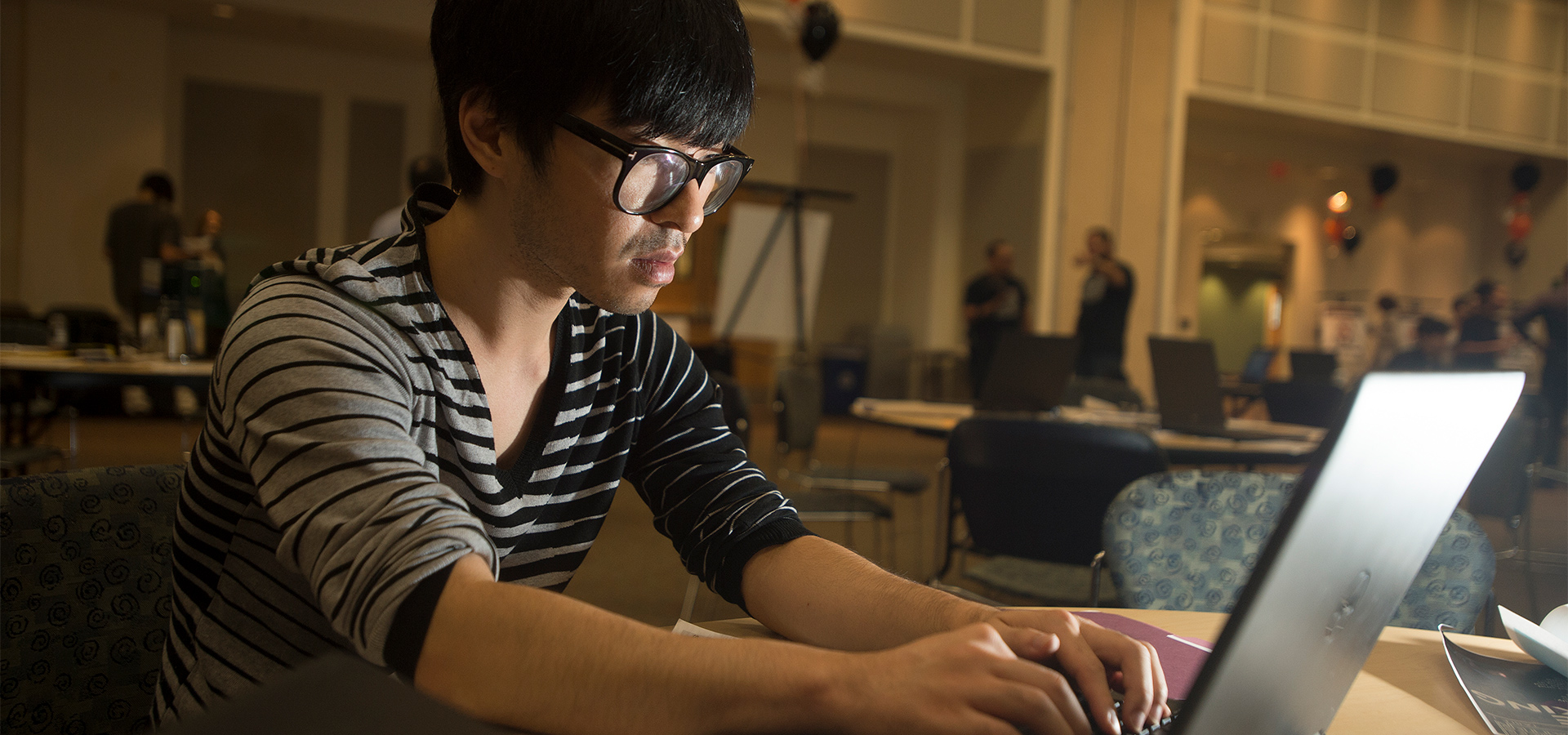 Student with a laptop coding during the Cybersecurity Fair