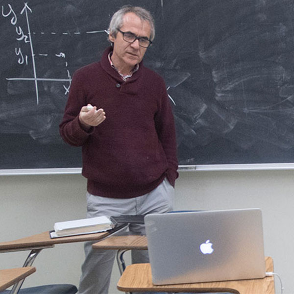 Faculty member teaching physics on his laptop