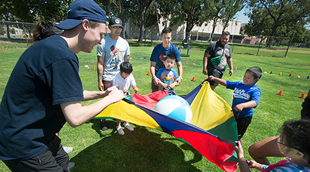 Students work with children and parachute