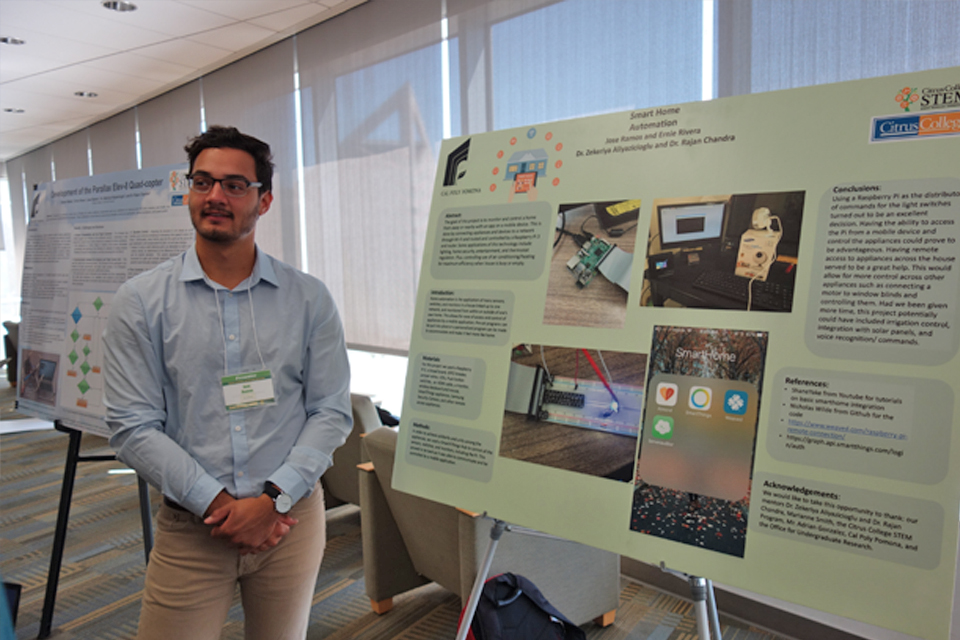 Student posing in front of poster presentation at research conference