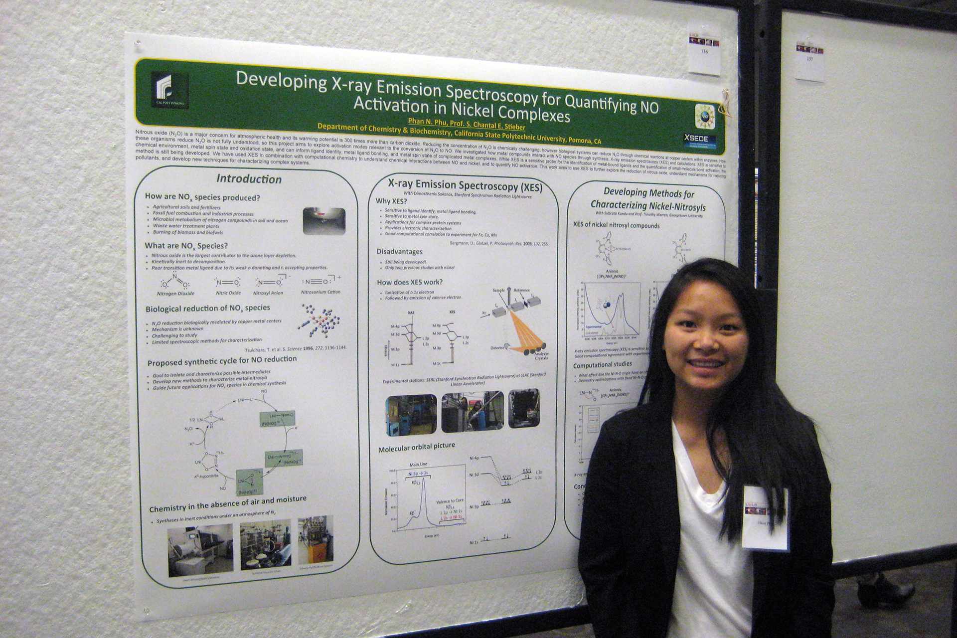 Student standing in front of their research poster at research conference