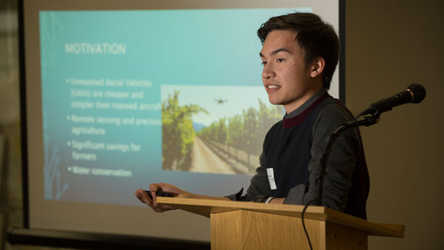 Student presenting research at a podium at research event