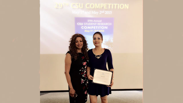 Student holding an award and standing next to mentor at competition
