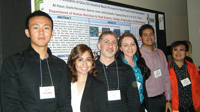 Group of research students posing in front of their research with their mentor