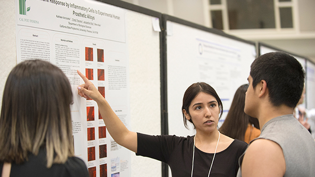 Student pointing at poster at a research event