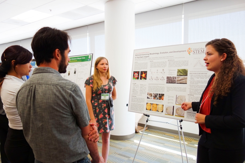 Two students standing in front of their poster presentation engaged in conversation with guests