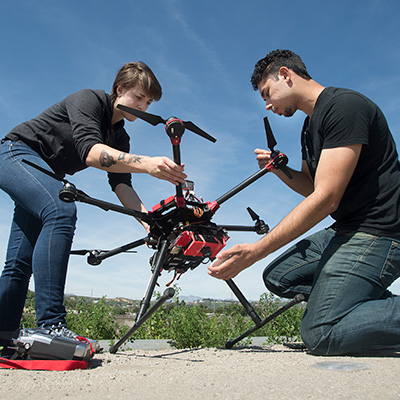 two students working with a drone