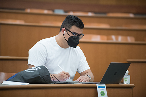 A student works on a laptop in the College of Business Administration study spaces room.