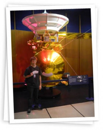 Alec poses in front of a scale model of the Cassini spacecraft