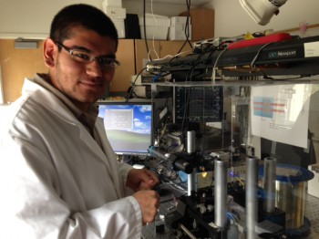 Martin Sanchez prepares optical fiber for tapering in Dr. Ertan Salik's lab.