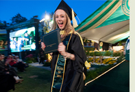 A Cal Poly Pomona graduate holding a diploma during Commencement