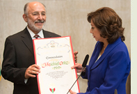 Cal Poly Pomona President Michael Ortiz receives a proclamation commending him for his lengthy career of outstanding service in higher education from Los Angeles County Supervisor Hilda Solis.