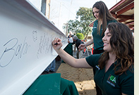 Participants sign a construction beam used in the Collins College of Hospitality Management's expansion project.