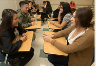 Students face each other in a classroom during first day of classes