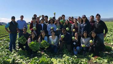 Students pose for a group photo in a farm field clutching heads of lettuce.