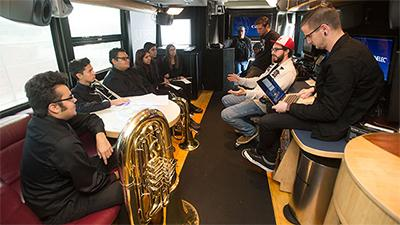 With instruments in hand, Garey High School music students listen to ideas about the music video aboard the John Lennon Bus.