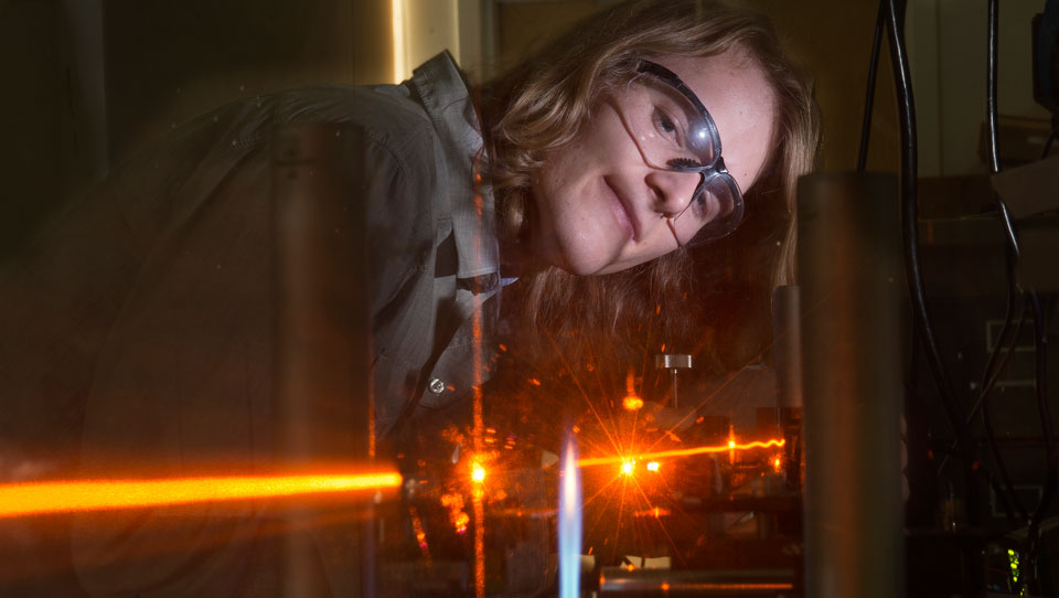 Student Conor Rowland works with helium laser rig